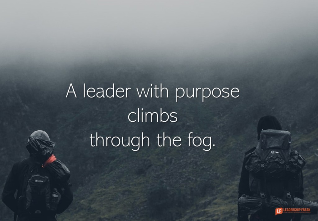 Foggy mountain.   A leader with purpose climbs through the fog.