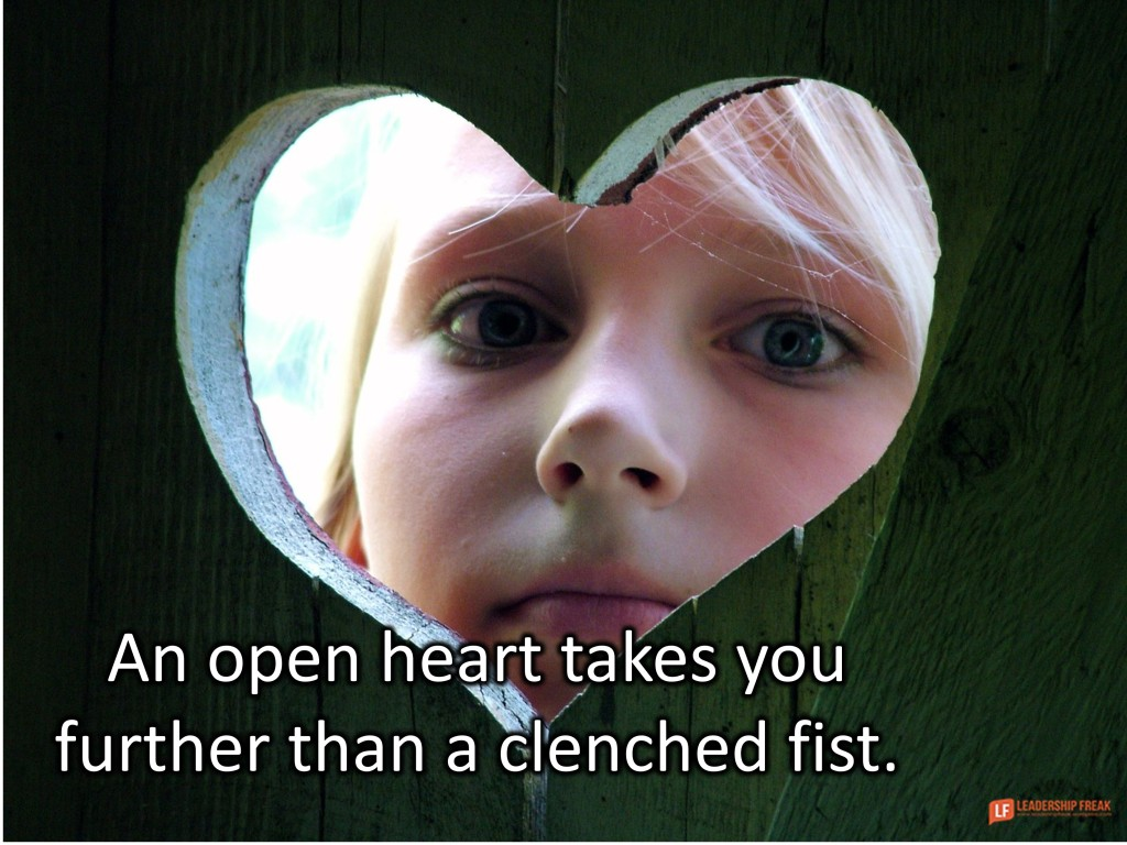 Image of a little girl looking through a heart-shaped hole in a fense.  An open heart takes you further than a clenched fist.